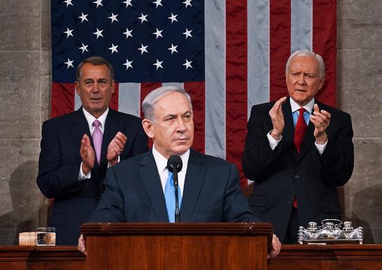 """[בתמונה: נאום בנימין נתניהו בקונגרס האמריקני. מאחוריו, ג'ון ביינר, יו""""ר בית הנבחרים דאז (משמאל); ואורין האץ', הנשיא הזמני של הסנאט דאז (מימין). התמונה היא נחלת הכלל]"""