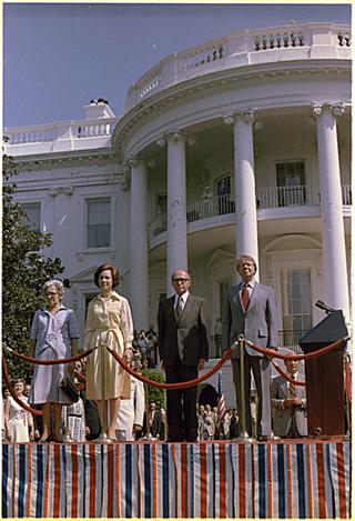 [בתמונה משמאל: פחות מחודש לאחר היבחרו, קבלת פנים חגיגית לראש הממשלהמנחם בגיןורעייתועל ידי הנשיא קרטר ורעייתו בוושינגטון, 19 ביולי 1977]