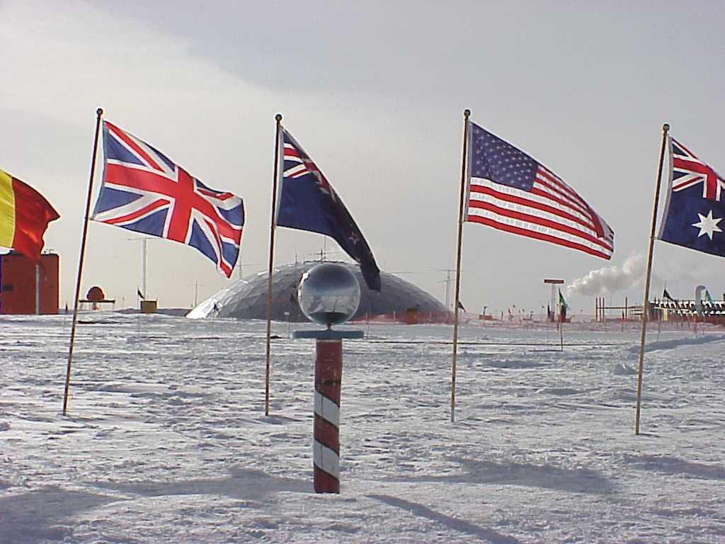 [בתמונה: מקומו הסמלי של הקוטב הדרומי. דגלי המדינות שחתמו עלההסכם האנטארקטי מסודרים סביבו. ברקע ניתן לראות את הכיפה הישנה של תחנת הקוטב. הכיפה זזה מהמקום המדויק של הקוטב הדרומי בשל תזוזת מדף הקרח שעליו היא יושבת... התמונה היא נחלת הכלל]